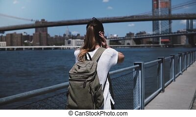 Camera follows young female tourist with backpack enjoying...