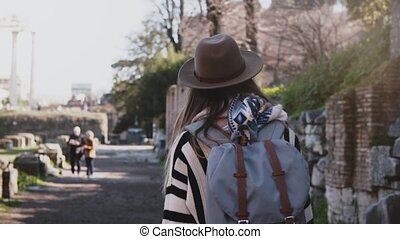 Camera follows young female traveler in hat with backpack exploring ruins of the Forum in Rome, Italy on vacation trip.