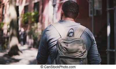 Camera follows young relaxed local man with backpack walking...