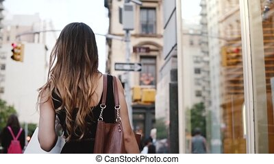 Camera follows young successful businesswoman walking along the street in New York City after shopping slow motion.