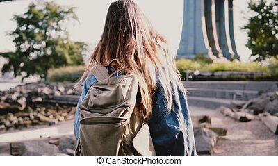 Camera follows young traveler girl with backpack walking along beautiful sunny Brooklyn Park river bank slow motion.
