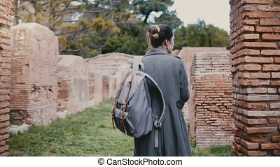 Camera follows young woman with backpack walking among ancient red brick ruins in Ostia Antica, Italy, on vacation trip.