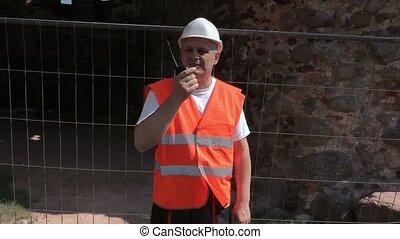 Camera goes around builder near fence