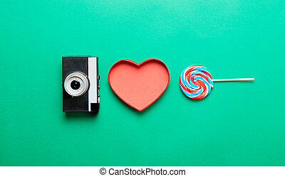 camera, heart shaped box and lollipop