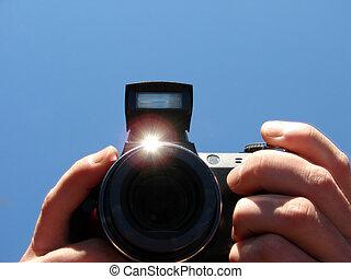 camera in hands - black digital camera in hands...