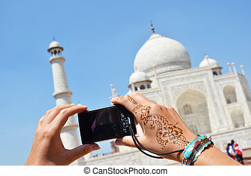 Camera in the hands pointing to Taj Mahal. Agra, India