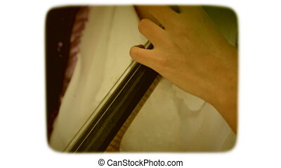 camera is transferred from neck to the body of the contrabass. woman is musician