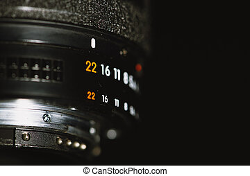 Camera lens with aperture numbers on a black background