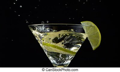 Bright Cocktail with Falling Lime on Dark Background.