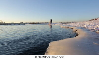Camera move along frozen coast to embracing bride and groom.