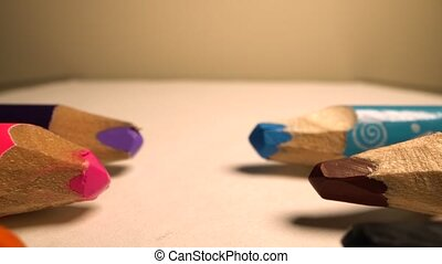 Camera moves above rows of colored pencils. Wooden pencils lie opposite each other in a row. White background. Super macro shot