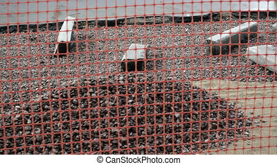 camera moves along a barrier of the building site of repair...