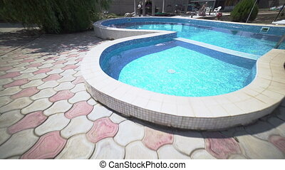 Camera moves along private swimming pool with paved deck at...