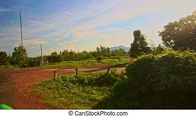 Camera Moves along Shady Sunny Road among Rural Landscape -...