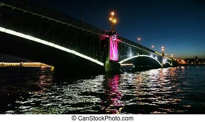 Camera moves at night under lighted iron bridge standing on Neva