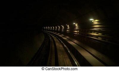 Camera Moves Backward along Metro Rails in Dark Tunnel