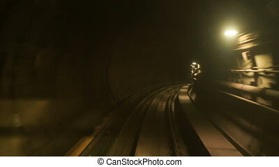 Camera Moves Forward along Metro Rails in Dark Tunnel