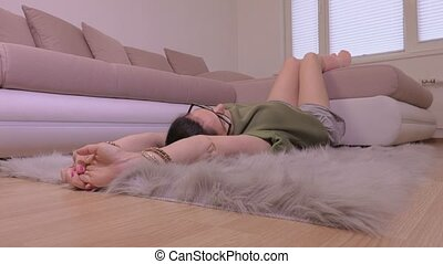 Camera moves on women who relaxing on faux fur rug