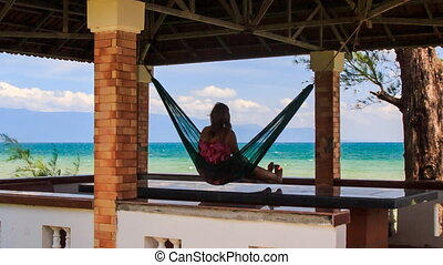 Camera Moves to Girl in Hammock in Red Roof Pavilion on...