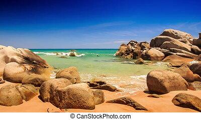 Camera Moves to Shallow Azure Sea Stones on Beach - camera...