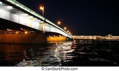 Camera moves under lighted Liteyny Bridge standing on Neva -...