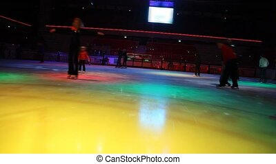 camera moving in skating rink with illumination past people