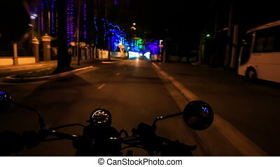 Camera on Motorcycle Moves along Dark Street by Lit Sideroads