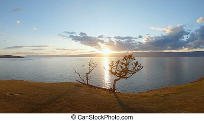 Camera on tripod filming a scenic seascape at sunset. Aerial...