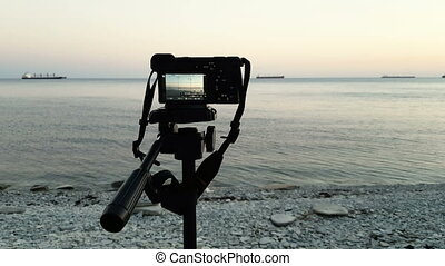 Camera on tripod takes video with tankers in the sea