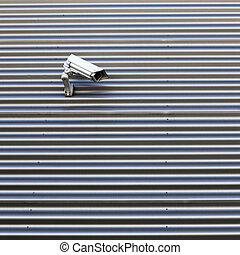 camera on wall of corrugated iron building