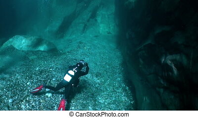 Camera operator diver underwater in transparent river...