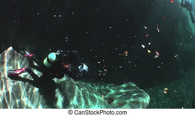 Camera operator in refraction of sunlight underwater in...