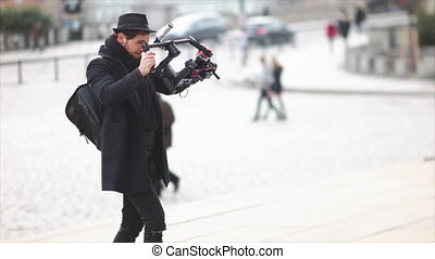 Adult caucasian movie maker walking with electronic stabilizer and making stock footage