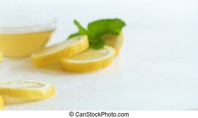 Camera panning along lemons, leaves of mint and jar with bee honey on white wooden table