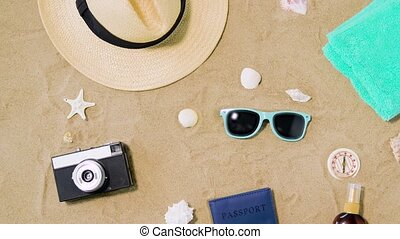 camera, passport, sunglasses and hat on beach sand