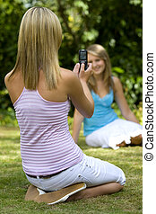 A beautiful young woman bathed in summer sunshine takes a picture of her friend using a mobile phone
