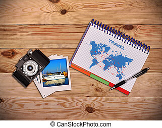 Camera, photo and notepad with drawing air travel scheme. Work desk tourist.