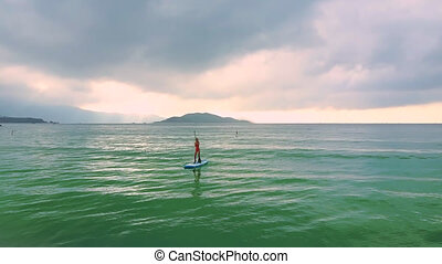 camera removes from girl on paddleboard to sand beach