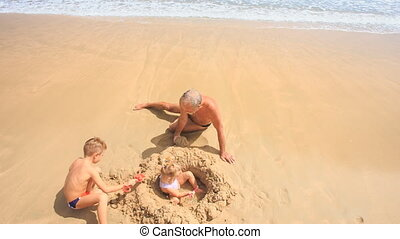 Camera Removes from Grandpa Kids Play among Sand Heap on Beach