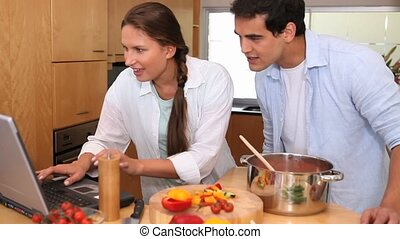 Camera rises to show a couple cooking together as they add ...