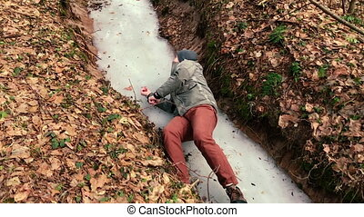 Camera shoots as a man rises who slipped on the ice in the forest.