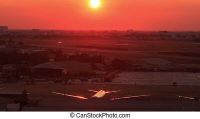 Camera Shows Sun Disk above Airfield Airplane at Sunset -...