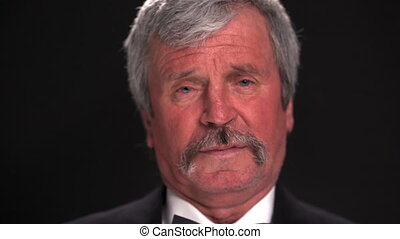 Camera slide out of an old grey haired man in an expensive tuxedo looking at the camera in a dark room isolated on a black background. Prores 422.