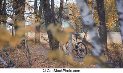 camera watches from behind the trees for the person who goes with the bike in the woods