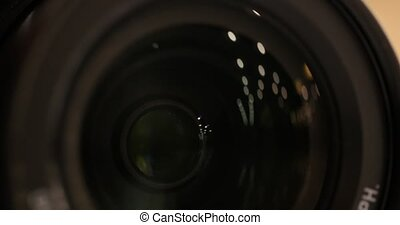 Camera zoom. Closeup shot of professional video camera, with its lens zooming in and out.