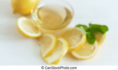 Camera zooms and focuses on lemons with honey lying on white wooden table