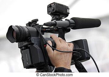 Cameraman and video camera - Hand of the cameraman holding...