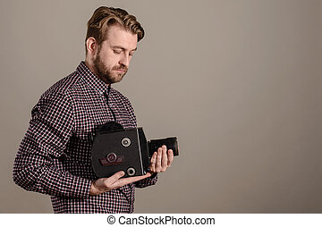 Cameraman in a checkered shirt gently holds an old movie camera in his hands