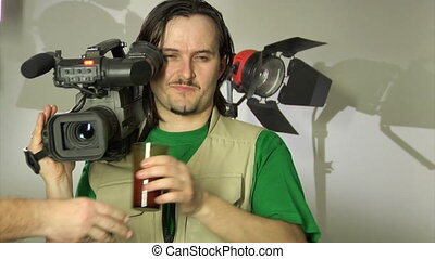 cameraman in studio - cameraman drinking juice as short...
