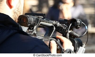 Cameraman is filming a reportage - Back of a cameraman who...